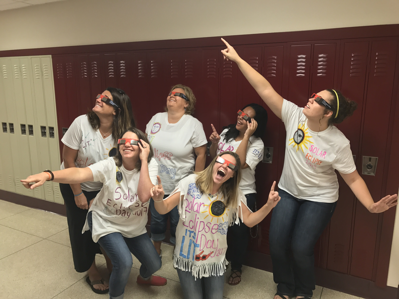 PCMS teachers strike a pose in the eclipse shirts they designed.